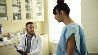 A transgender woman in a hospital gown speaking to her doctor a transgender man in an exam room