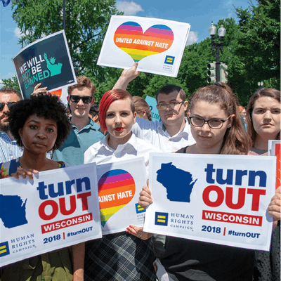 "A crowd of people holding signs that say ""Turn Out Wisconsin""."