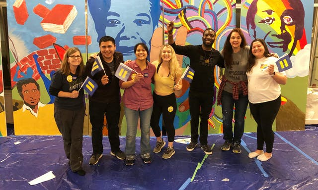 Group of people holding small HRC flags in front of a colorful mural