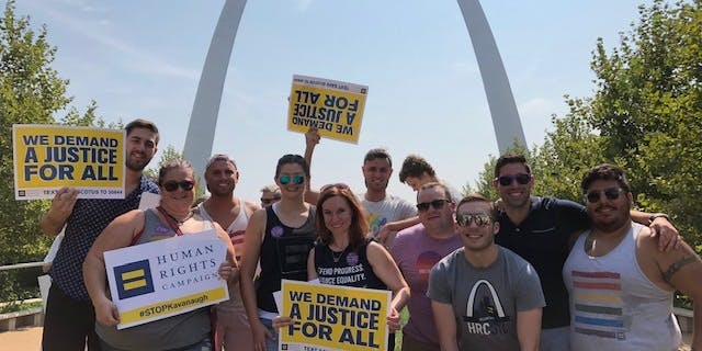 "People with signs that say ""we demand justice for all"" in front of the st louis bend"