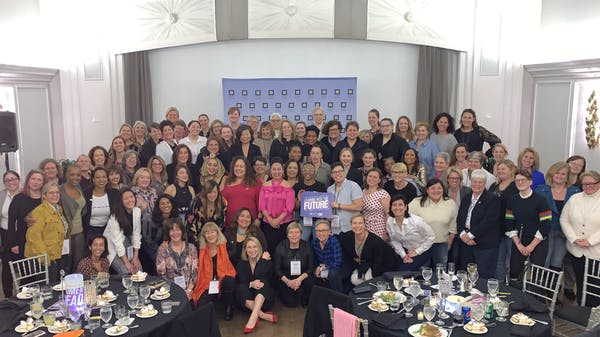 Large group of women gathered in a ballroom, all smiling and huddled together