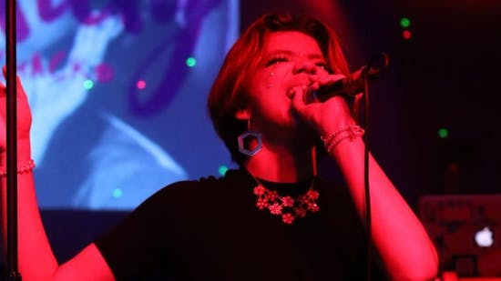 Young person singing on stage with pink lighting