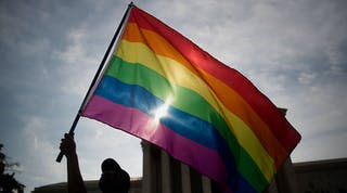 A large rainbow flag is waved in front of the US Supreme Court.