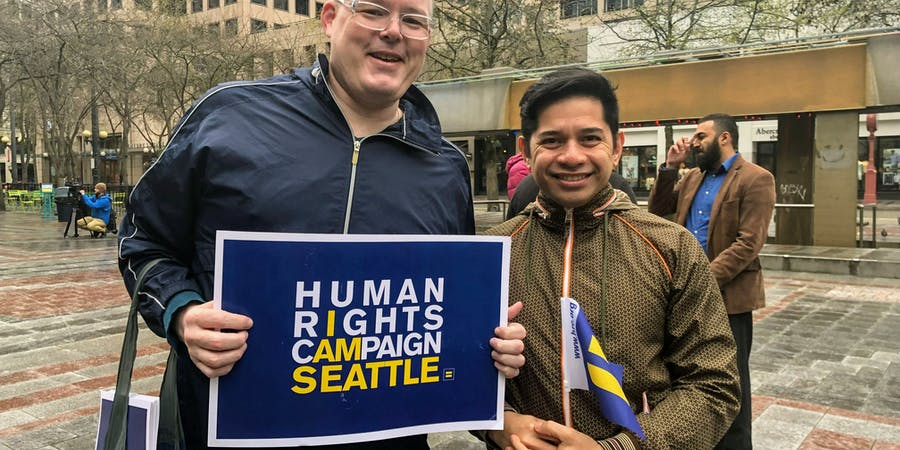Two people standing together holding a HRC Seattle sign