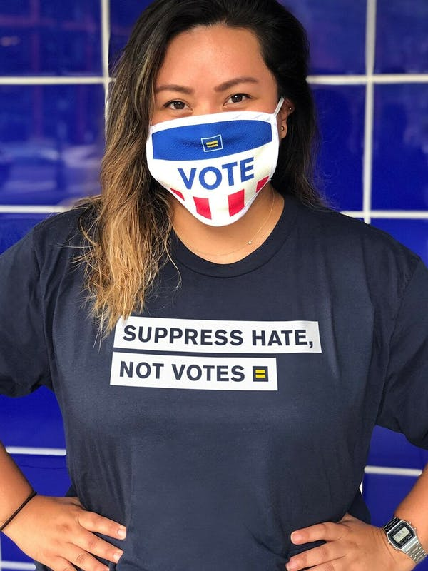 "Person wearing an HRC shirt that says ""Suppress Hate, Not Votes"" and a ""Vote"" face mask."