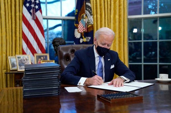 President Joe Bien signs a document at his desk in the Oval Office.