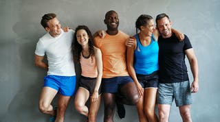 Group of people wearing fitness apparel standing against a gray wall