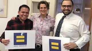 Three people together holding HRC signs