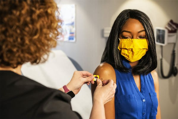 A woman of color receives a bandaid after a vaccine.