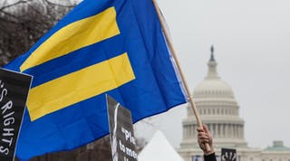 HRC flag with blue background and yellow equal sign flies in front of U.S. Capitol